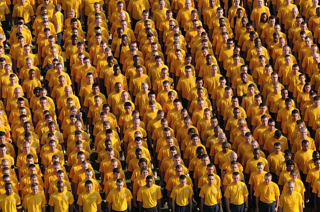 Crowd of people in rows and columns wearing yellow tee shirts