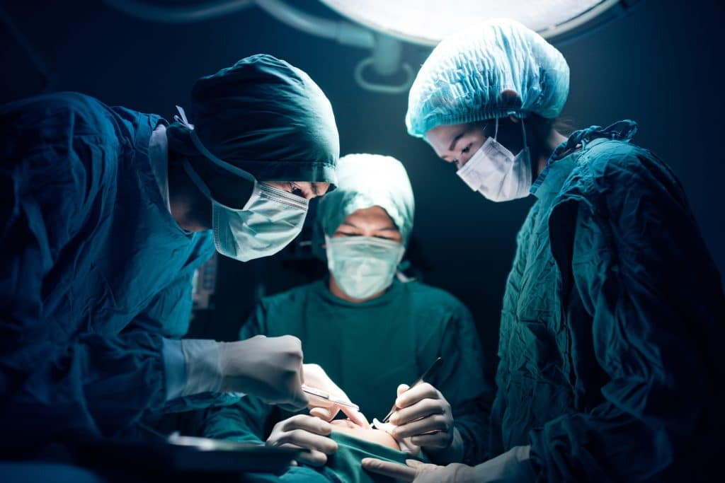 Three peopel in doctor's surgical scrubs with caps and masks performing surgery on patient under overhead light.