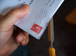 close up image of corner of envelope in person's hand with red stamp that has been postmarked with wavy lines