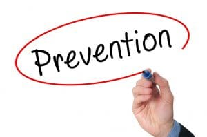 The word prevention is drawn in black ink, and a man's hand holding a marker has just circled the word in red ink.