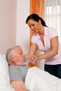 A young female nursing aide holding a water glass up for an older male nurisng home resident in bed, assisting him with drinking to prevent nursing home dehydration