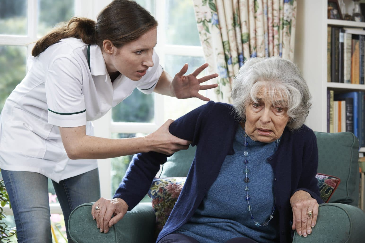 A caregiver commits elder abuse by screaming at a nursing home resident.