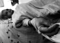 An elderly person lays helpless because of negligence, abuse, and neglect caused by over-medication in a nursing home.