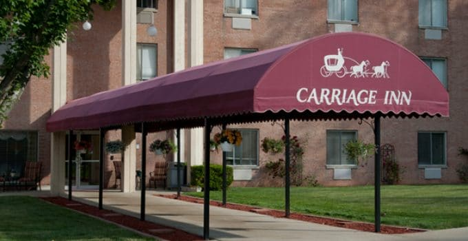 Photo of outside of building with red awning over walkway that reads Carriage Inn in white letters.