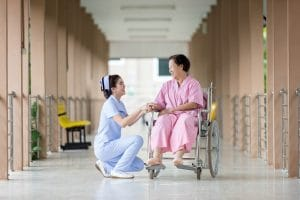 Photograph of nursing home hallway with nurse in blue scrubs kneeling next to and looking at woman in wheelchair wearing pink robe.