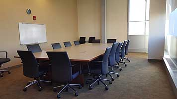 Image of beige room with conference table surrounded by 14 rolling office chairs