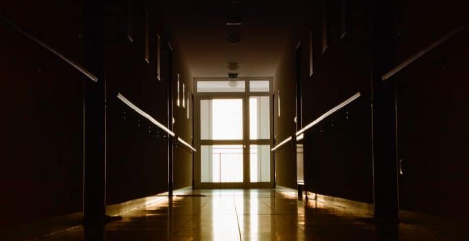Long hallway with unattended door at the end