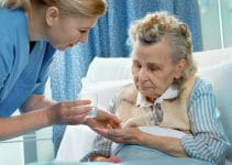 a nurse gives a senior medicine