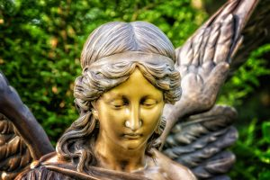 Photo of bronze statue of female angel from the shoulders up with green foliage background