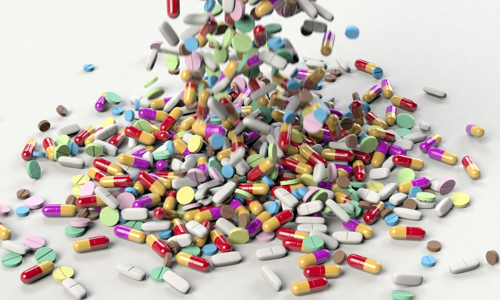 Variety of pills of different colors spilling onto a white table to suggest over medication of nursing home residents.