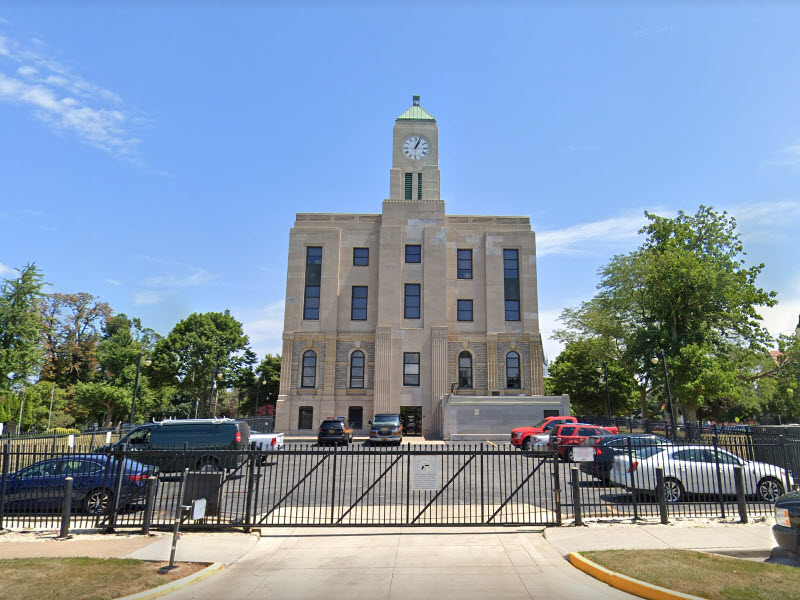 Courthouse with clock tower and gated parking lot